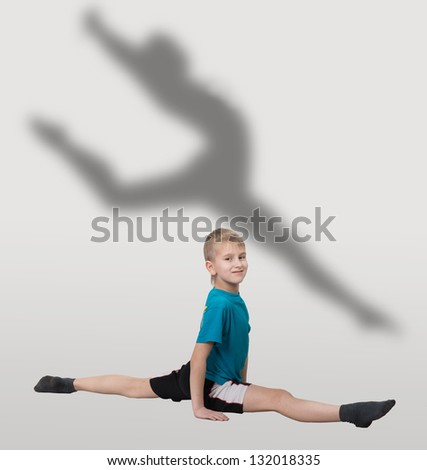 Smiling boy doing horizontal splits with dancer's silhouette behind him - stock photo
