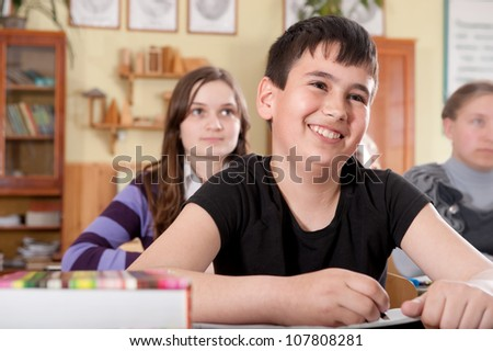 Smiling boy during a lesson at elementary age school - stock photo