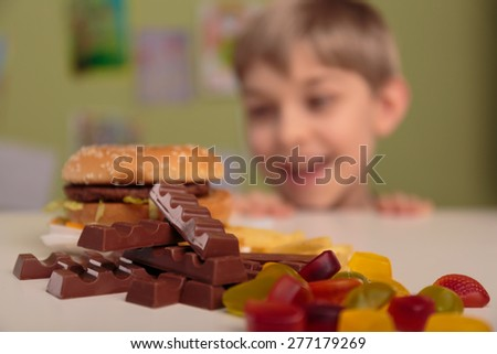 Smiling boy enjoying his unhealthy school lunch - stock photo
