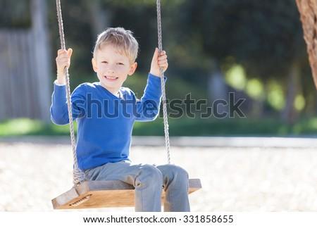 smiling boy enjoying swinging at the park - stock photo
