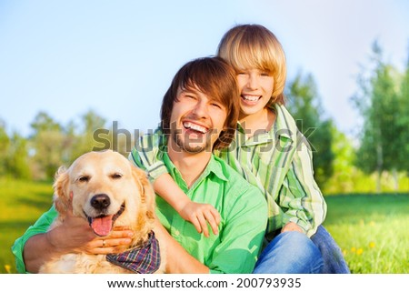 Smiling boy, father and dog sit in park on grass - stock photo