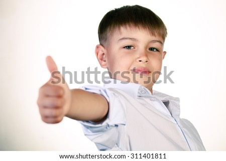 Smiling boy gesturing with his thumb up - stock photo