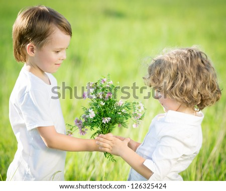 Smiling boy giving bouquet of spring flowers to happy girl
