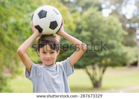 Smiling boy holding a soccer ball in the park on a sunny day - stock photo