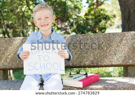 smiling boy holding back to school sign ready for school year - stock photo