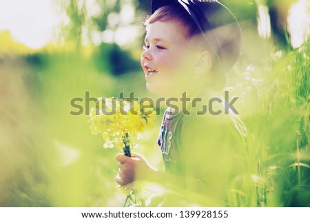 Smiling boy holding flowers - stock photo