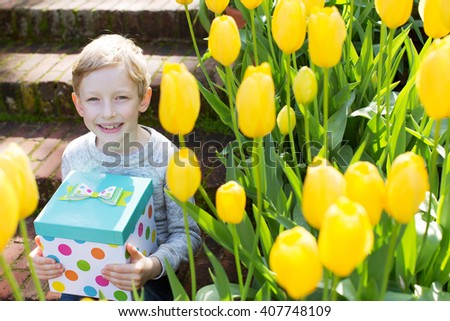 smiling boy holding nice present at spring blooming time - stock photo