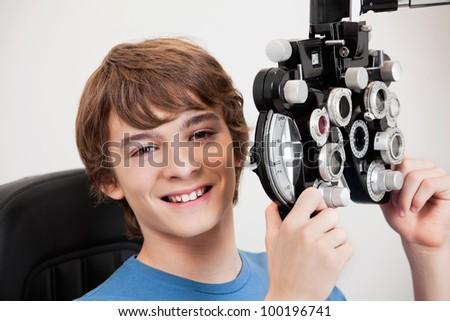 Smiling boy holding phoropter while undergoing an eye examination. - stock photo