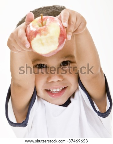 Smiling boy holds an apple with a bite out of it. - stock photo
