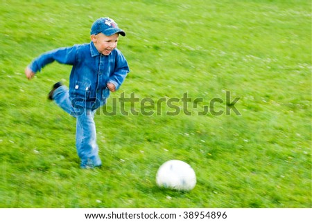 smiling boy in blue jeans playing football on green field - stock photo