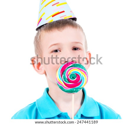 Smiling boy in blue t-shirt and party hat with colored candy - isolated on white. - stock photo