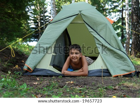 smiling boy in camping tent in forest - stock photo