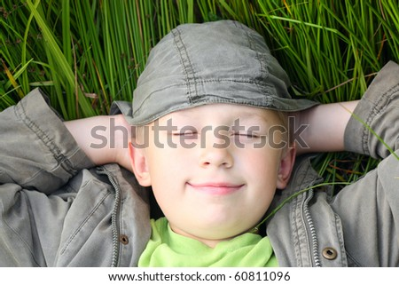 Smiling boy in green grass. - stock photo