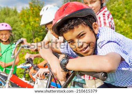 Smiling boy in helmet holds handle-bar of bike - stock photo