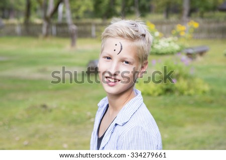 Smiling boy  in nature sunny day. On the forehead shows (drawn) smile icon. Concept of positive thoughts and emotions.