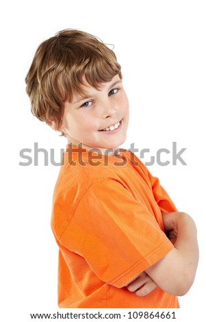 Smiling boy in orange t-shirt with folded arms stands half-turned - stock photo