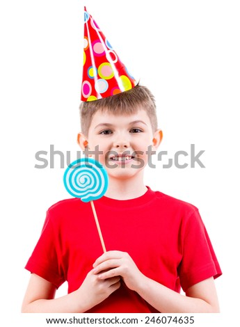 Smiling boy in red t-shirt and party hat holding colored candy - isolated on white. - stock photo