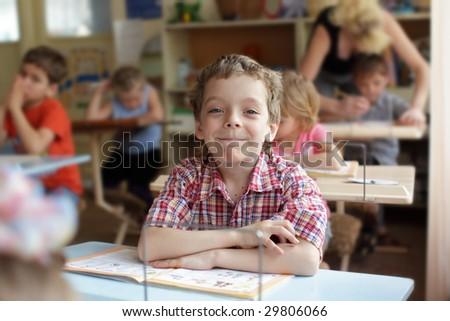 Smiling boy in school class - stock photo