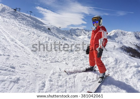 Smiling boy in ski suit on the snow