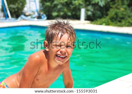 Smiling boy in the swimming pool on summer vacations - stock photo