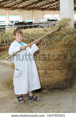 Smiling boy in white coat loads hay by big pitchfork at large cow farm.  - stock photo