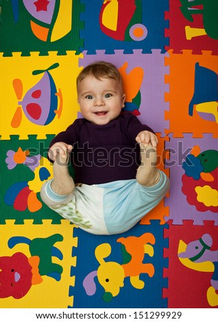 smiling boy is lying on a puzzle with animals and transport - stock photo