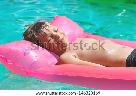 Smiling boy lies on pink mattress in the pool - stock photo