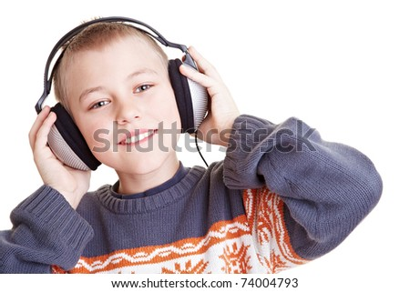 Smiling boy listening to music with headphones - stock photo
