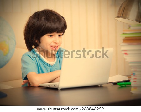 smiling boy looking at a computer monitor, distance learning. instagram image retro style - stock photo