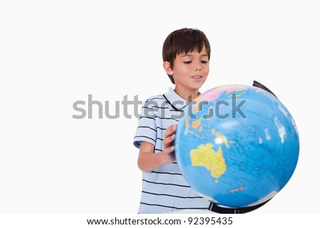 Smiling boy looking at a globe against a white background - stock photo