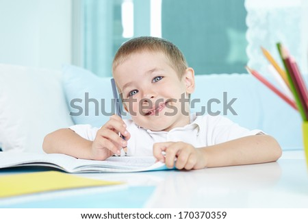 Smiling boy looking at camera while drawing - stock photo