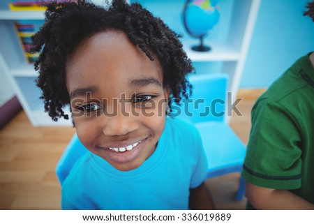 Smiling boy looking at the camera at their desk
