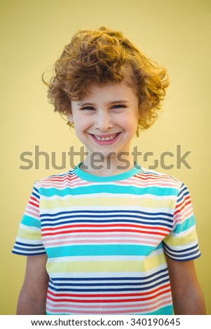 Smiling boy looking at the camera while standing - stock photo