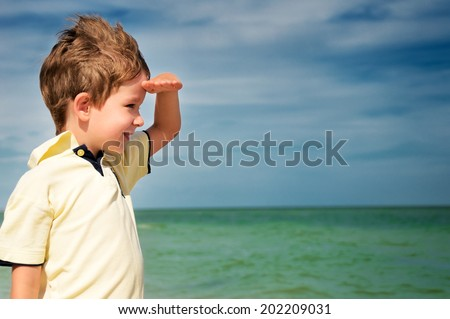 smiling boy looking away from his palm on the background of cloudy sky and sea. horizontal - stock photo