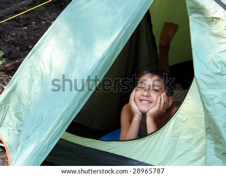 smiling boy looking from camping tent - stock photo