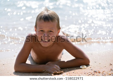smiling boy lying on the beach - stock photo