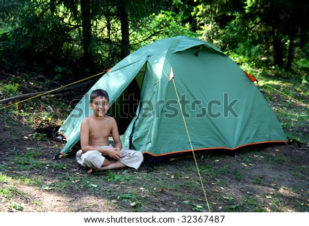 smiling boy near camping tent in summer forest - stock photo