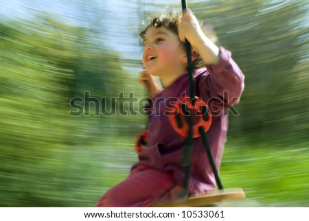 smiling boy on a swing with motion blur - stock photo