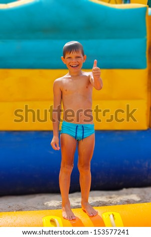 Smiling boy on blue swimming trunks during his summer vacation - stock photo