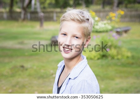 Smiling boy on green background in nature sunny day. Concept of positive thoughts and emotions.