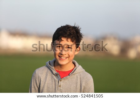 Smiling boy outside in the golden hour near sunset - warm tones