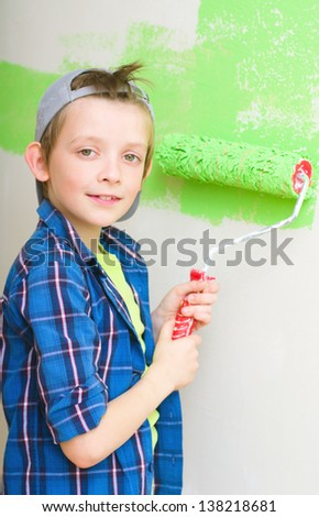 Smiling boy painting interior wall of home - stock photo