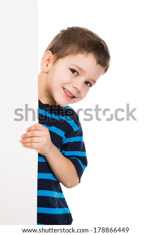 Smiling boy peek out from vertical empty banner, isolated on white - stock photo