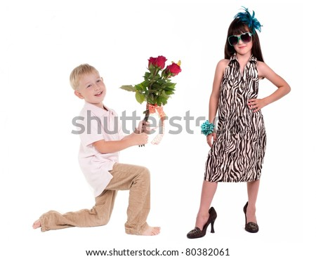 Smiling boy presenting bunch of red roses to charming girl isolated on white background