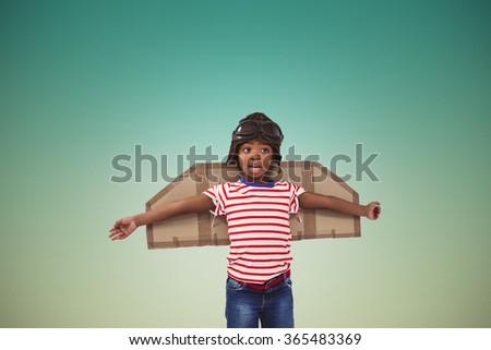 Smiling boy pretending to be pilot against blue sky - stock photo