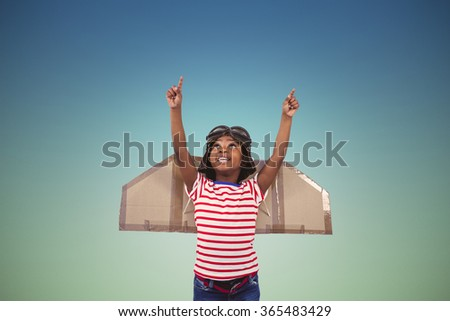Smiling boy pretending to be pilot against blue sky - stock photo