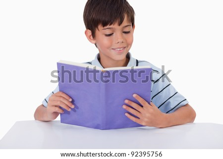 Smiling boy reading a book against a tablet computer - stock photo