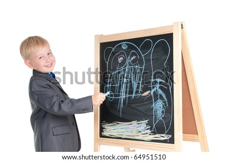 Smiling boy showing the drawing he made on a blackboard - stock photo