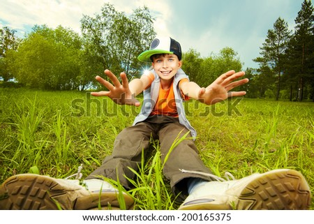Smiling boy sitting on a grass at a park. Summer day.  - stock photo