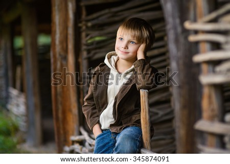 smiling boy sitting on fence in the garden - stock photo